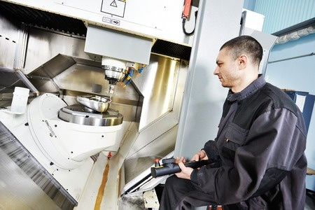 Operator performing precision CNC machining