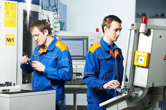 Operators performing precision CNC machining